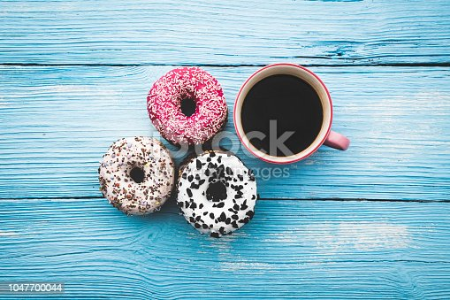 Coffee cup and colorful donuts on wooden blue background. Top View