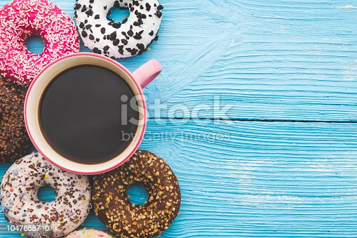Coffee cup and colorful donuts on wooden blue background with space on text. Top View