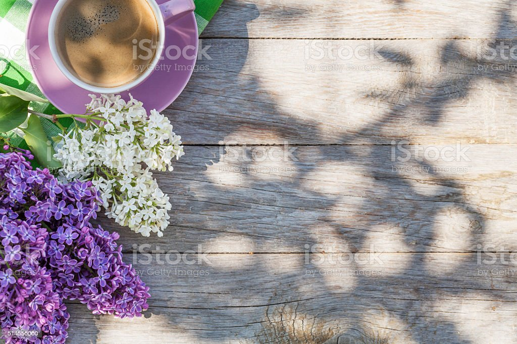 Coffee cup and colorful lilac flowers on garden table stock photo