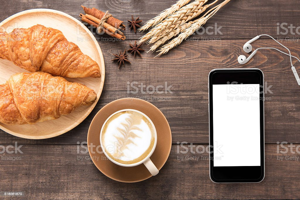 Coffee cup and fresh baked croissants, earphones, smartphone on stock photo
