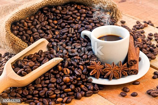 519529874 istock photo coffee cup and grains on wooden table 530543253