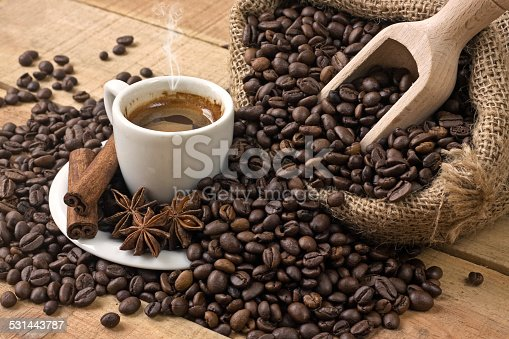 519529874 istock photo coffee cup and grains on wooden table 531443787