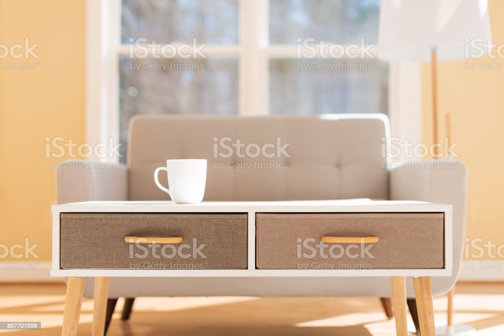 Coffee cup and gray midcentury loveseat stock photo