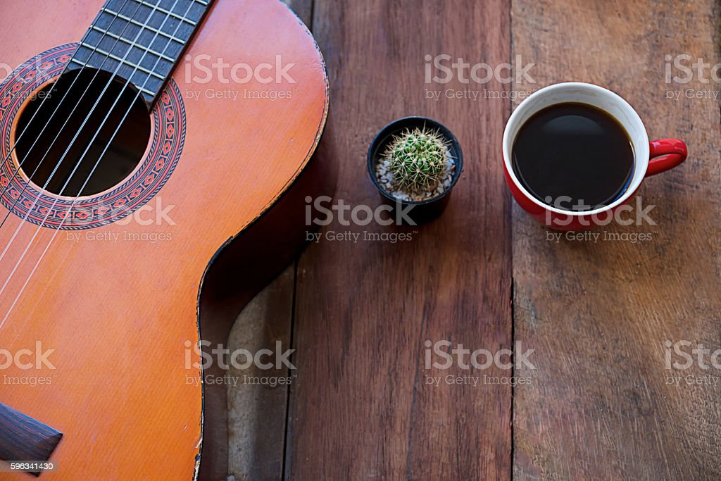 coffee cup and guitar on wooden table royalty-free stock photo