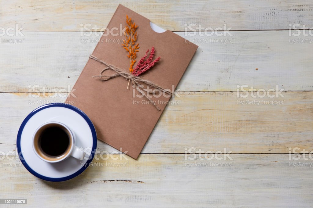 Coffee cup and handmade gift card on wooden table stock photo
