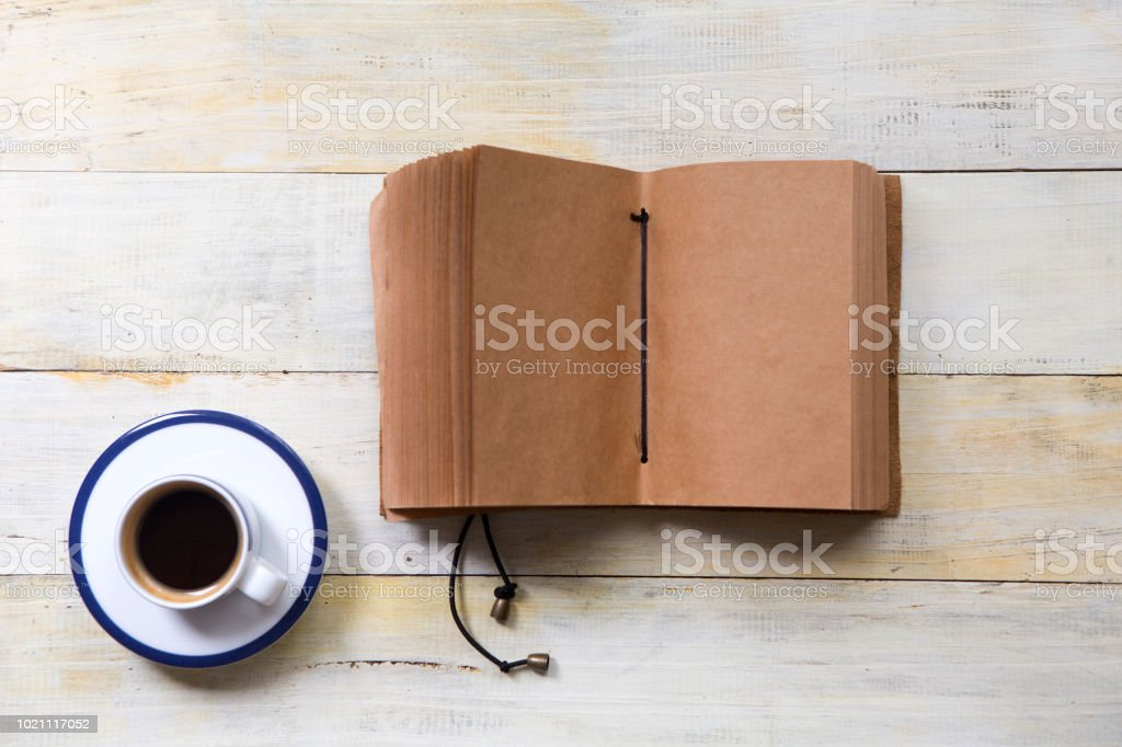 Coffee cup and handmade notebook on wooden table stock photo