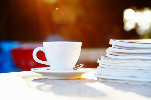 Coffee cup and magazines