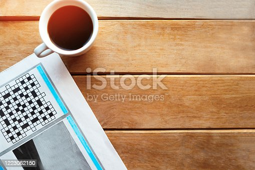 Coffee cup and newspaper on wooden table. Copy space for the text