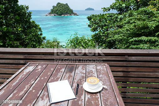Coffee cup and notebook on the wooden table at the sea view terrace