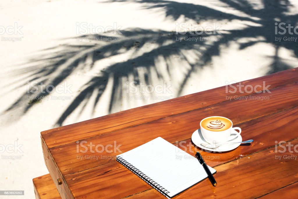 Coffee cup and notebook on the wooden table at tropical beach Lizenzfreies stock-foto