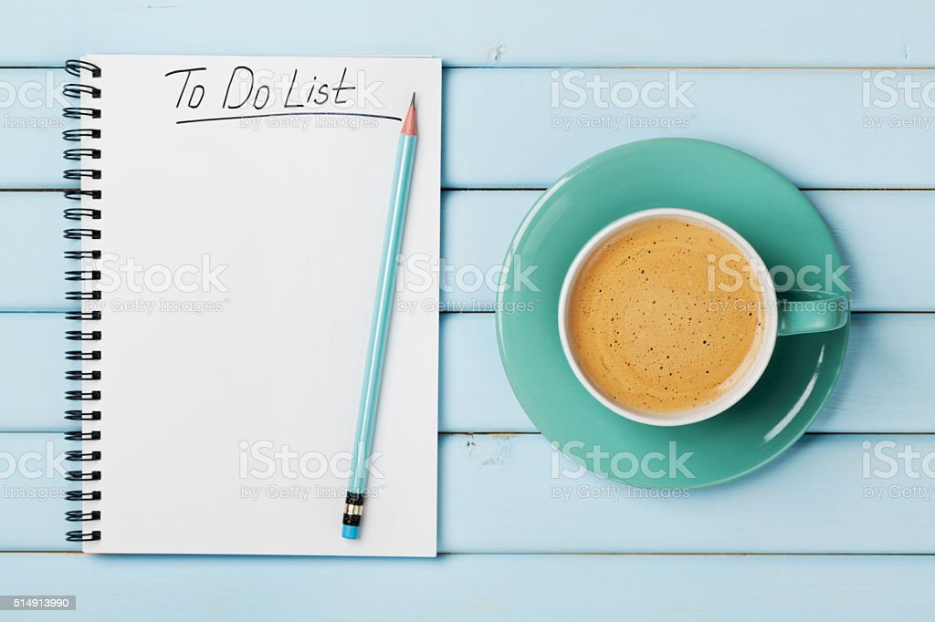 Coffee cup and notebook with to do list on desk stock photo