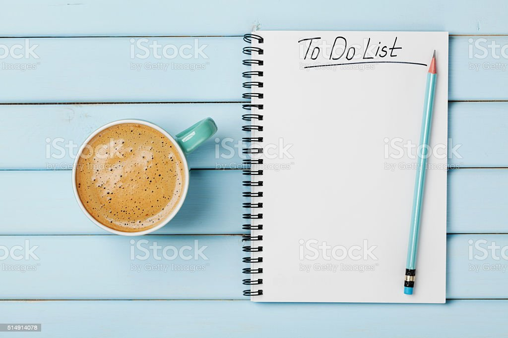 Coffee cup and notebook with to do list, planning concept stock photo