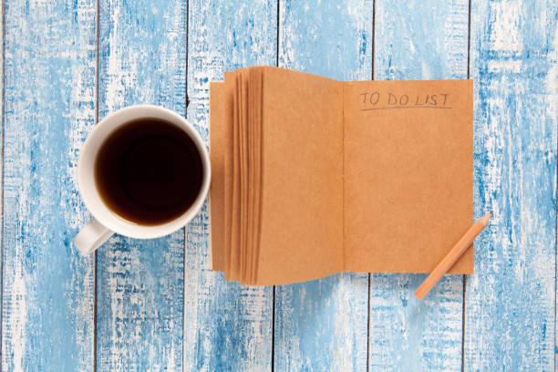 Xícara de café e caderno com lista de tarefas, fazer conceito de planejamento - foto de acervo