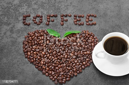Coffee cup and roasted  beans in the shape of the heart.