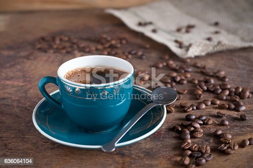 istock Coffee cup and roasted beans on a wooden background 636064104