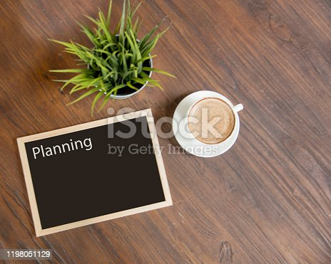 914465180 istock photo Coffee cup and small tree decorate on wooden table with copy space. Background banner for coffee lover. 1198051129