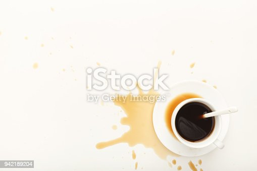 istock Coffee cup and spilt espresso on white background 942189204