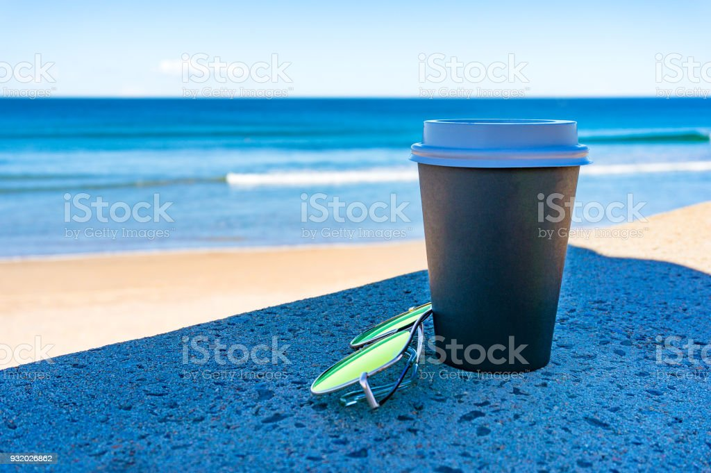 Coffee cup and sunglasses with beach on the background stock photo