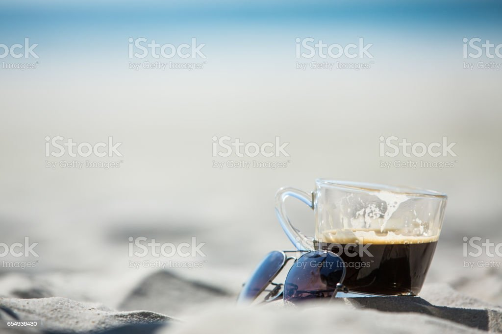Coffee cup and Sunglasses with sand & sea background stock photo