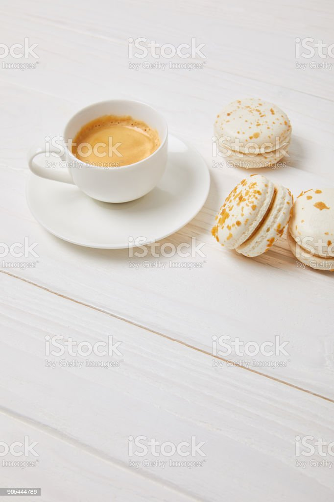 coffee cup and three macarons on white wooden table zbiór zdjęć royalty-free