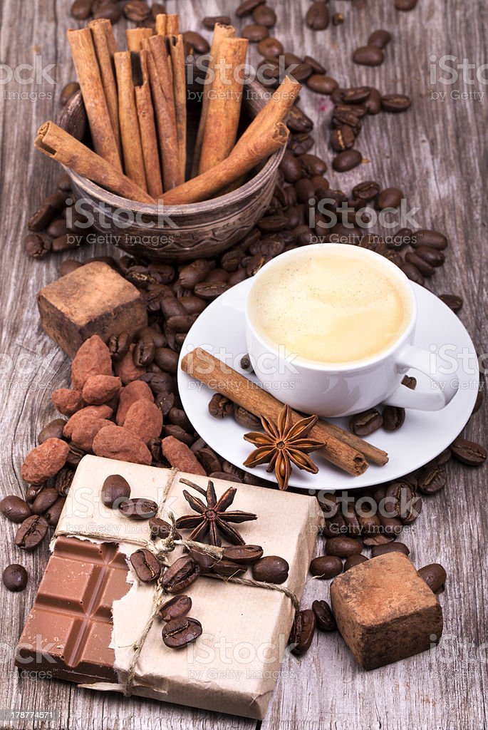 Coffee cup, beans, cinnamon, anise and sweets royalty-free stock photo