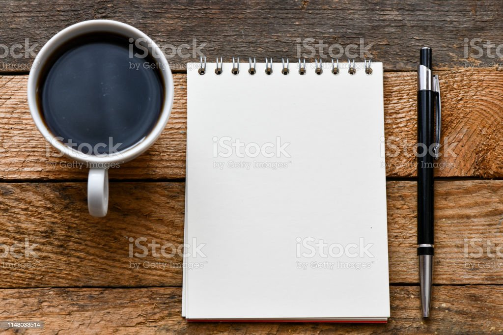 coffee cup, blank notepad and pen on wooden background, top view stock photo