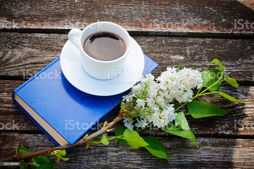 Coffee cup, book and white lilac flower on wooden background