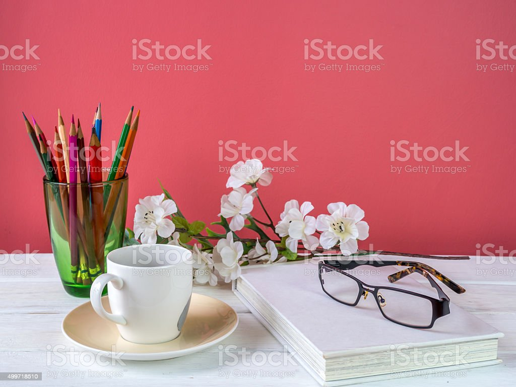 Coffee cup, book, artificial flower on table/ interior still life stock photo