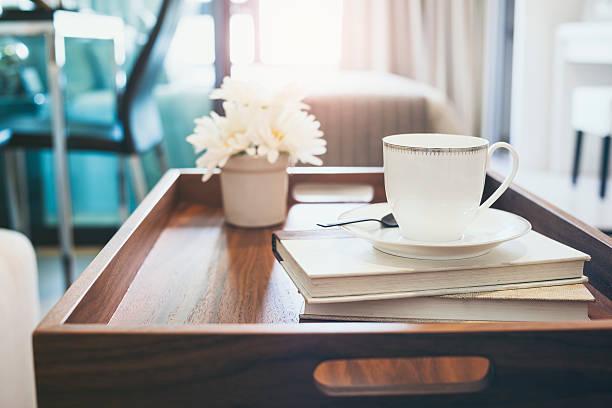 kaffeetasse buchen sie weiße blume auf hölzernen tablett innendekoration - tischsofa stock-fotos und bilder