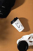 istock Coffee cup. Fresh delicious coffee in a white paper glass with print on a brown background. Top view 1299806497