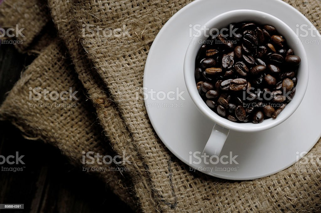 coffee cup full of beans against hessian sack royalty-free stock photo