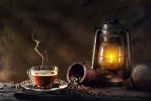Coffee cup glass and vintage kerosene lamp oil lantern burning with glow soft light aged wood floor
