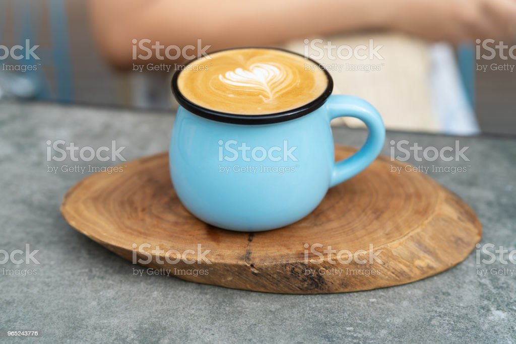 Coffee cup in blue glass on wooden plate royalty-free stock photo