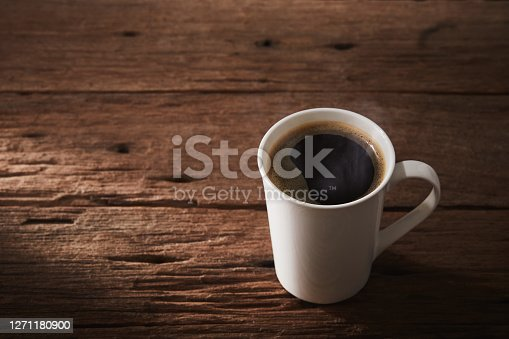 Coffee cup is hot drink on wooden with sunlight