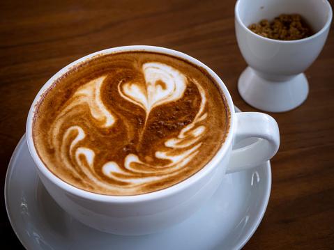 Coffee cup latte art on wood table