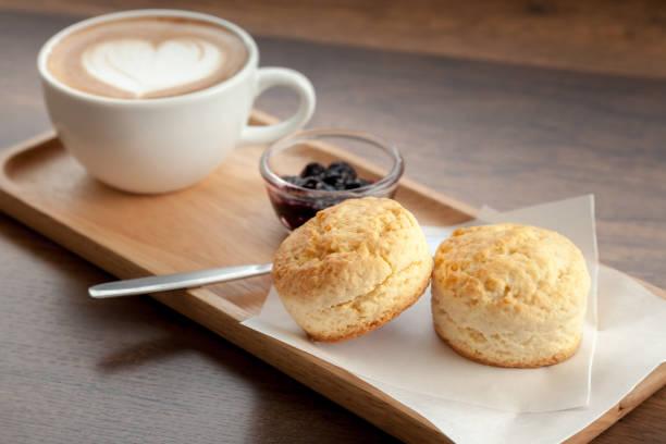 kaffeetasse latte mit scones und hausgemachter heidelbeermarmelade auf holzhintergrund serviert (selektiver fokus) - scones backen stock-fotos und bilder