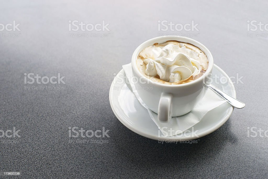 Coffee cup on gray table with whipped cream royalty-free stock photo