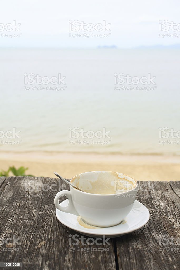 Coffee cup on grunge terrace facing seascape royalty-free stock photo