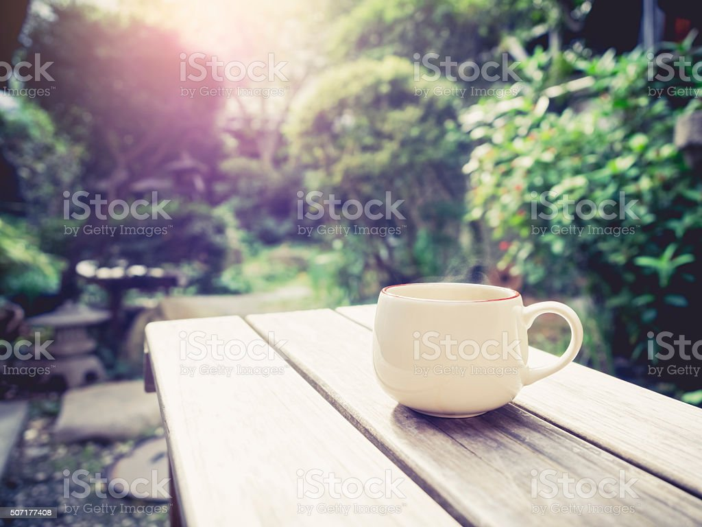 Coffee cup on table Outdoor in garden with Sunrise stock photo