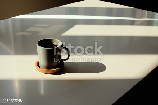 Coffee cup on table photo taken in natural sunlight