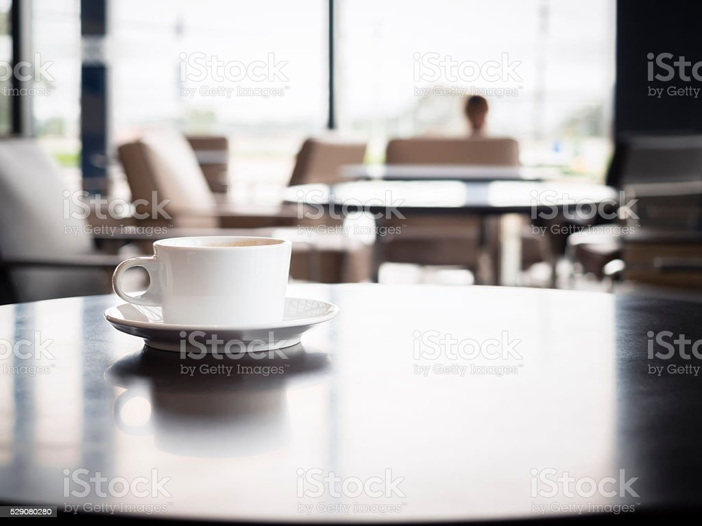 Coffee cup on table with blurred people in Restaurant Interior stock photo