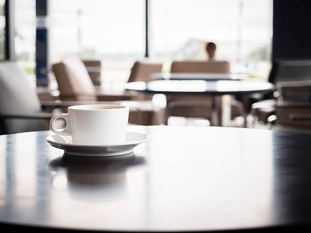 テーブルの上のコーヒーカップ、ぼやけた人のレストランのインテリア - airport lounge ストックフォトと画像