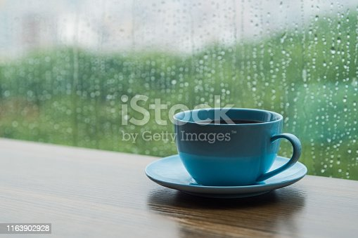 Coffee cup on table with raindrops falling on window