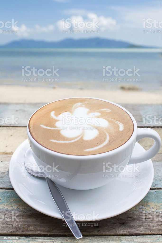 Coffee cup on terrace facing seascape stock photo