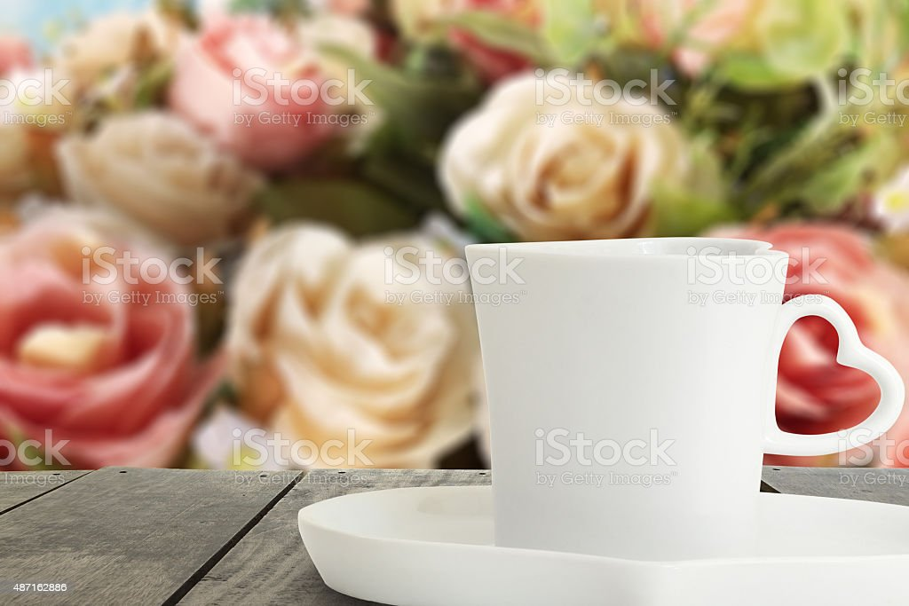 Coffee cup on the terrace wood and rose blur background stock photo