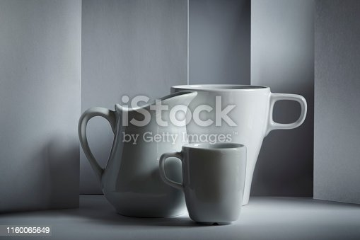 White mug on white table. Soft light is coming from the window casting shadows. Beside is a smaller espresso cup and cream jug or milk jug. Front view.