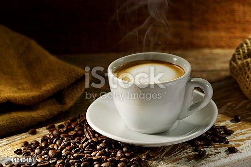 Xícara de Café preto em fundo de madeira com grãos de café, paus de canela. Bebida quente saindo fumaça