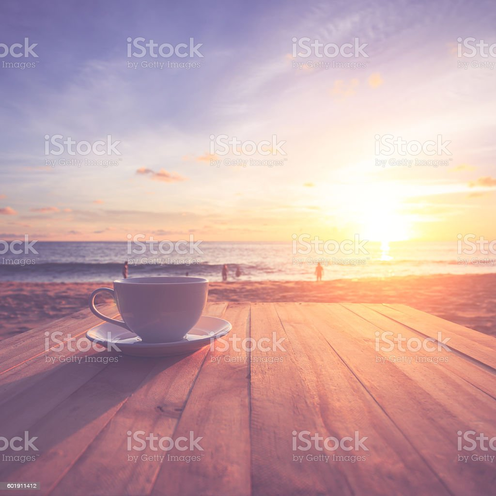Coffee cup on wood table at sunset or sunrise beach stock photo