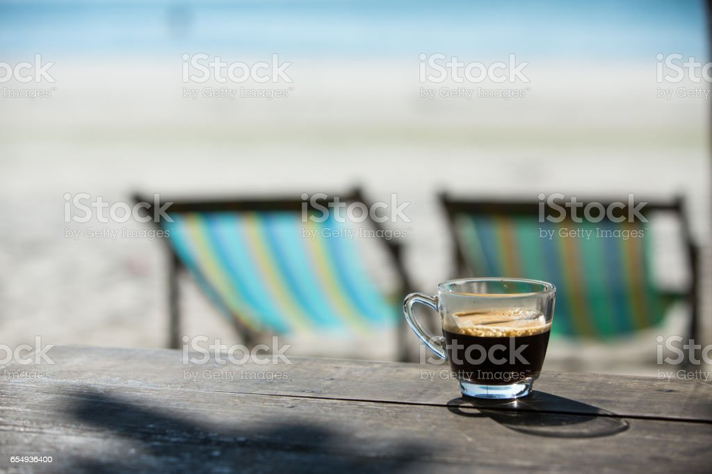 Coffee cup on wood table with sea & sand background stock photo