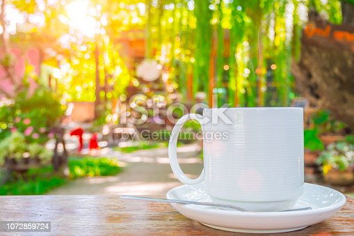 istock coffee cup on wooden table green outdoor nature garden background. 1072859724